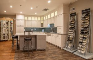 A kitchen remodeling showroom with a beautiful model of a modern kitchen and samples being displayed.